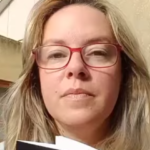 Fotografia da escritora Cláudia Machado a segurar o livro de O Acordo